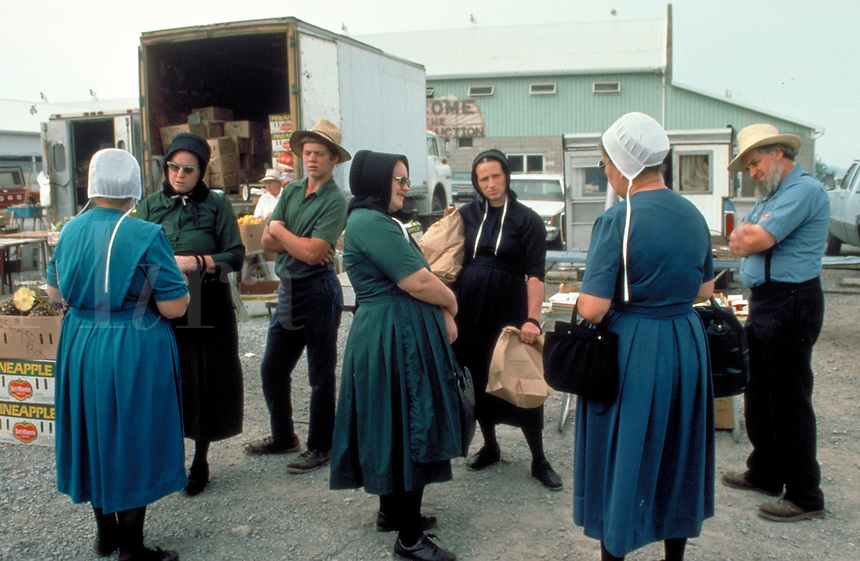 At the community market several married Amish men and women and a male youth talk near the produce. Amish men and women. Kidron Ohio United States market.