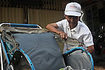 A cyclo driver prepares for work in the early morning hours on Bui Vien Street in Ho Chi Minh City, Vietnam. Aug. 27, 2011.