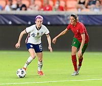 HOUSTON, TX - JUNE 10: Megan Rapinoe #15 of the United States looks to pass the ball with Silvia Rebelo #4 of Portugal closing in on her during a game between Portugal and USWNT at BBVA Stadium on June 10, 2021 in Houston, Texas.