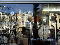 The reflected image on a shop window of a Parisian square, with a parked car and a traffic light on the background of some characteristic modern buildings.  Across the shop window one can distinguish different objects: There are some clocks that appear to be on the building roofs, a globe, and some Oriental objects in foreground, in a confused and colorful atmosphere (Paris, 2007).<br /> <br /> L'immagine riflessa sulla vetrina di un negozio di una piazza Parigina, con un'automobile parcheggiata ed un semaforo sullo sfondo di alcuni edifici moderni caratteristici. Attraverso la vetrina si possono distinguere diversi oggetti: ci sono degli orologi che sembrano stare sui tetti degli edifici, un mappamondo ed alcuni oggetti Orientali in primo piano, in un'atmosfera confusa e colorata (Parigi, 2007).