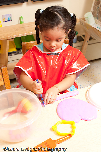 Education preschool 3-4 year olds art activity girl playing with play dough vertical