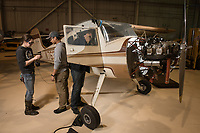 From left; Aviation Maintenance students Kaasan Braendel, Desmond Corpuz, and Roland Rodriguez work on an aircraft after removing its wing in the hangar at UAA's Aviation Technology Complex on Merrill Field.
