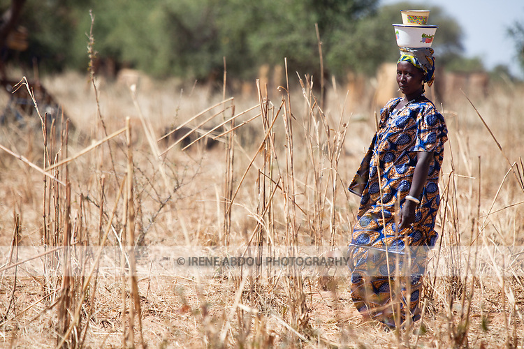"""In West Africa, certain villages have markets that """"assemble"""" at regular intervals, such as weekly or every three days.  People from villages around the region come on market day to buy and sell food, livestock, and other goods and services.  Here, a woman carries goods on her head to the village market of Bourro in northern Burkina Faso."""
