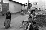 Indigenous Mexican women in traditional dresses Zapotec Tehuantepec Hand Embroidered Huipil from Oaxaca celebrating at village festival in 1970s Tehuantepec Oaxaca. Mexico Food being carried in basket on her head with a balloon on a stick. 1973.