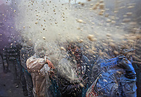 Pictured: A flour wars participant throws yellow coloured flour in Galaxidi, Greece. Monday 19 February 2018<br /> Re: Clean Monday (Monday of Lent) celebration of flour wars (Alevromoutzouroma) in the town of Galaxidi, which coincides with the beginning of the Greek Orthodox Lent in Greece. The origins of the custom are unclear, however it appears in its current form since the mid-19th century.<br /> Locals and visitors of all ages gather to collect large quantities of flour which they throw to each other. Various types of coloring is added for effect while people paint their faces with charcoal.