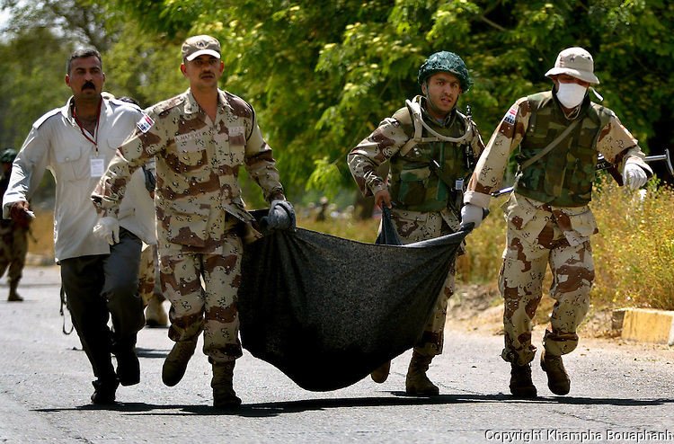 ICDC personnels transport a corp at the scene of a suicide car bomb that killed Iraqi Governing Council President Izzedin Salim in Baghdad, Iraq on May 17, 2004.  (photo by Khampha Bouaphanh)