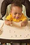 10 month old baby boy sitting in high chair pincer grasp picking up small snack food pieces