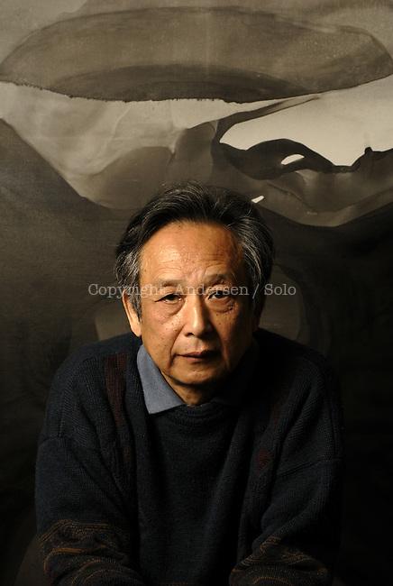 Gao Xingjan in his studio in Paris with his paintings.