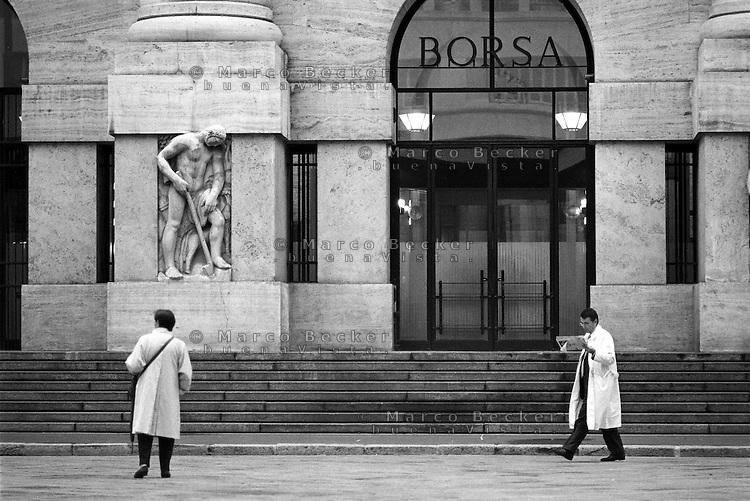 Milano, piazza Affari. Palazzo Mezzanotte, sede della Borsa. Un uomo legge il giornale --- Milan, Affari square. Palazzo Mezzanotte, seat of the Italian stock exchange. A man reading the newspaper