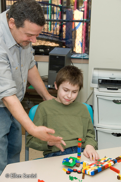MR / Albany, NY.Langan School at Center for Disability Services .Ungraded private school which serves individuals with multiple disabilities.Teaching assistant praises  childs' work with small building blocks. Boy: 10, Duchenne muscular dystrophy, expressive and receptive language delays.MR: Bud2; Sai2.© Ellen B. Senisi