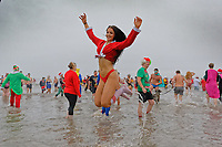Pictured: A young woman in a Santa outfit jumps in the sea. Tuesday 25 December 2018<br /> Re: Hundreds of people take part in this year's Porthcawl Christmas Swim in south Wales, UK.