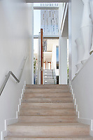 Multiple staircases descend the four storeys of this modern beach house