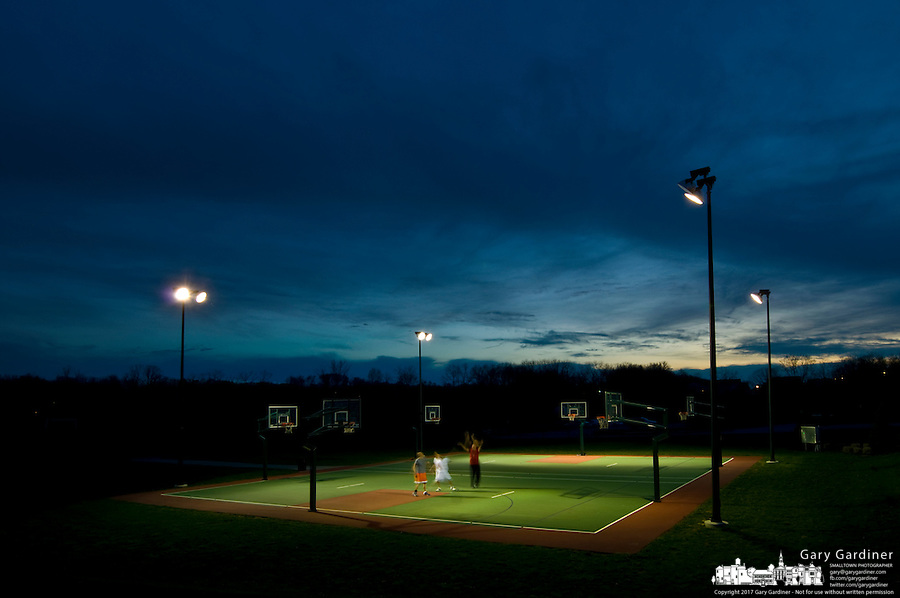 A father and his sons play on the outdoor court at sunset on the sports fields at the Westerville, Ohio, Community Center Sports Complex. Photo Copyright Gary Gardiner.