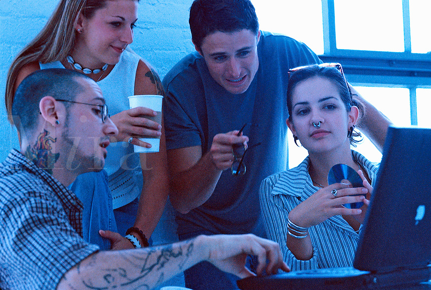 Young adults as they talk and work together at a business meeting in a casual office setting.