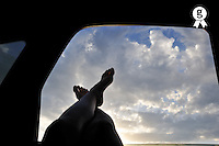 Woman's legs barefeet out of car window, sunset (Licence this image exclusively with Getty: http://www.gettyimages.com/detail/91537165 )