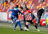 20th March 2021; Brentford Community Stadium, London, England; English Football League Championship Football, Brentford FC versus Nottingham Forest; Emiliano Marcondes of Brentford is challenged by James Garner of Nottingham Forest