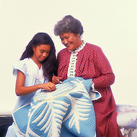 Tutu (grandmother) and granddaughter making a Hawaiian quilt