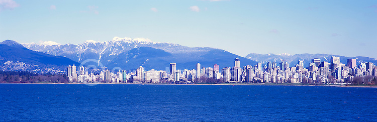 """City of Vancouver """"West End"""" and Downtown Skyline at English Bay, BC, British Columbia, Canada, in Spring.  Stanley Park is to the left midground, and the North Shore Mountains (Coast Mountains) rise above the City. - Panoramic View"""