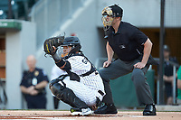Charlotte Knights catcher Alfredo Gonzalez (21) catches a pitch as home plate umpire Richard Riley looks on during the game against the Scranton/Wilkes-Barre RailRiders at BB&T BallPark on April 12, 2018 in Charlotte, North Carolina.  The RailRiders defeated the Knights 11-1.  (Brian Westerholt/Four Seam Images)
