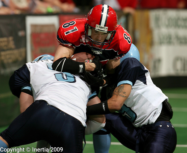 SIOUX FALLS, SD - MAY 9:  Ben Nelson #81 of the Sioux Falls Storm is brought down by a pair of defenders including Derrick Philips #5 of the Muskegon Thunder in the first quarter of their game Saturday night at the Sioux Falls Arena. (Photo by Dave Eggen/Inertia)