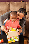 Two year old toddler boy with mother, putting blocks away, she is assisting by holding box flaps open
