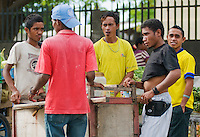 Men gather around a street vendor selling a variety of foods from a pushcart in Dili, Timor-Leste (East Timor)