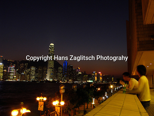 Men looking in the evening from Kowloon at Victoria Harbour and the skyline of Hongkongs Central District.