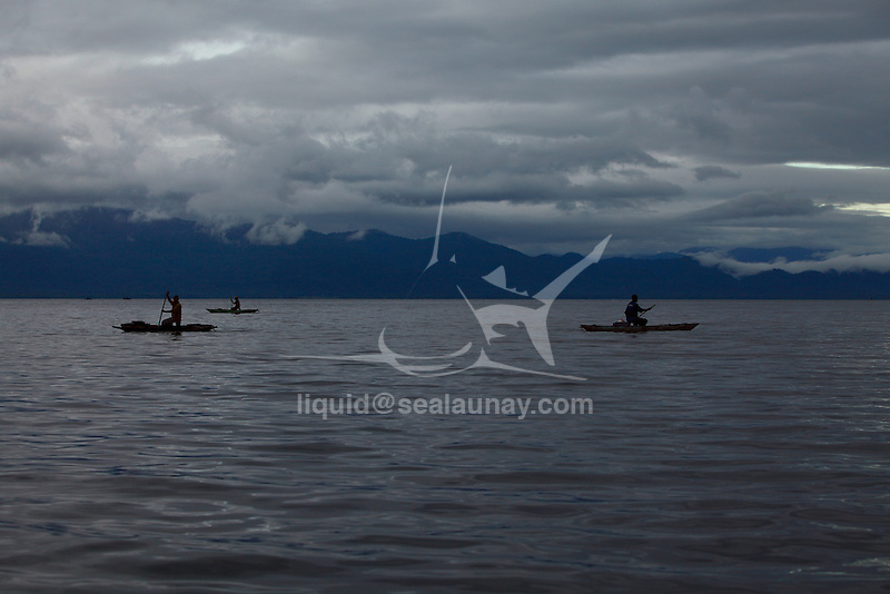 """Early morning fishermen on outrigger canoe in the Alotau Bay. Alotau is the capital of Milne Bay Province, a province of Papua New Guinea..The town is located within the area in which the invading Japanese army suffered their first land defeat in the Pacific War in 1942, before the Kokoda Track battle. A memorial park at the old battle site commemorates the event..Alotau became the provincial capital in 1969 after it was shifted from Samarai..Alotau is the gateway to the Milne Bay Province which contains some of the most remote island communities in the world. Renowned for its friendly people and amazing tropical islands, it is a very well kept secret and sees very few tourists each year. The whole of Milne bay offers some of the worlds best scuba diving and coral reef experiences..Alotau itself is a busy regional """"Outpost""""-like town. Most facilities are available here although it can be sporadic at times.."""