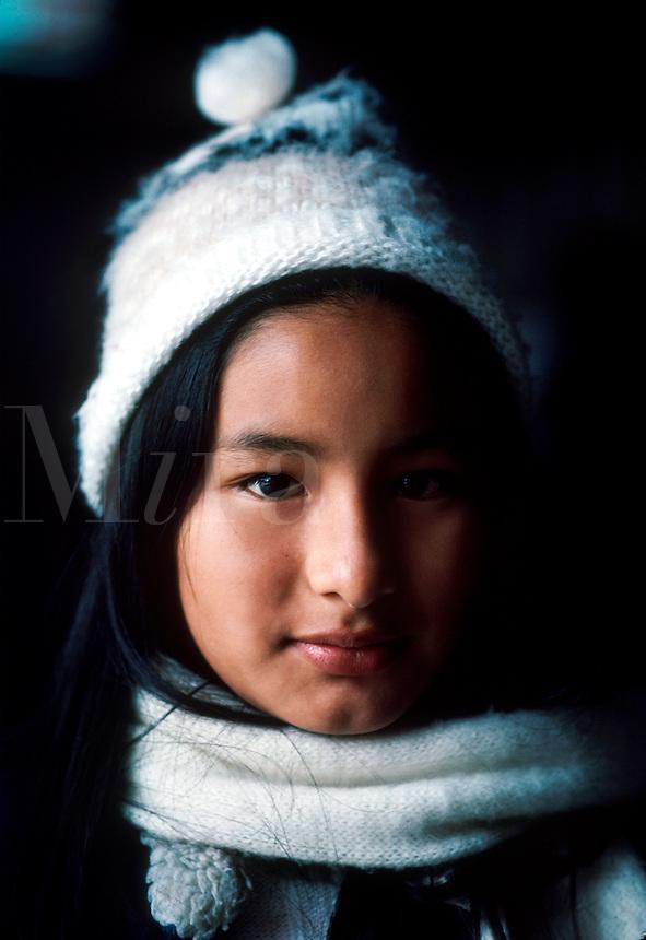 Portrait of a beautiful teen Peruvian girl wearing a warm woolen hat and scarf.