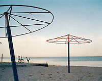 A man does a hand stand on a beach near metal sun shades in the town of Aktau, looking out over the Caspian Sea.