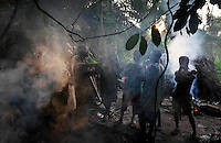 "Playing flutes at Camp.Pygmies playing hand made flutes in their hunting camp.  Paul Salopek talks about the light in the forest.  ""Rain forests are light-struck places. This comes as a surprise. Countless books and movies would have us believe otherwise. The world beneath a jungle canopy is neither dim, nor gloomy, nor monochrome. It glows with the light of some alien order - light so improbable it actually has a dreamed quality, the way colors in dreams possess actual weight, or create sound, or stop time.""."