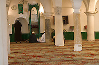 Tripoli, Libya - Al-Nagah Mosque, Tripoli Medina (Old City).  Tripoli's First Mosque, Rebuilt 17th Century.  Men Awaiting Prayer Time.  The indentation in the wall, the mihrab, indicates the direction of Mecca.  The imam stands on the green minbar to deliver his sermon.