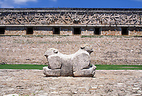 Uxmal - Stone carving of two-headed jaguar against background of stone wall with elaborate frieze. #5786. Uxmal Yucatan Mexico.
