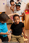 Education preschool 4-5 year olds pretend play group of boys and girls playing hairdresser or barber shop cutting and styling hair of classmates vertical