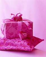 Close-up of a present beautifully wrapped in pink patterned paper and decorated with matching ribbon and flowers