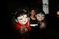 CHINA. Beijing. A woman posing for a picture with two statues in the shopping district of Wangfujing, a popular place for spectators, tourists and athletes to visit during the Olympic Games. 2008.