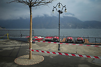 """Switzerland. Canton Ticino. Lugano. A police line forbids the access to the lake because of coronavirus (also called Covid-19). Due to the spread of the coronavirus , the Federal Council has categorised the situation in the country as """"extraordinary"""". It has issued a recommendation to all citizens to stay at home, especially the sick and the elderly. The Federal Council (German: Bundesrat, French: Conseil fédéral, Italian: Consiglio federale, Romansh: Cussegl federal) is the seven-member executive council that constitutes the federal government of the Swiss Confederation. From March 16 the government ramped up its response to the widening pandemic, ordering the closure of bars, restaurants, sports facilities and cultural spaces. Only businesses providing essential goods to the population – such as grocery stores, bakeries and pharmacies – are to remain open. Lake Lugano (also called Ceresio) is a glacial lake which is situated on the border between southern Switzerland and Northern Italy. 22.03.2020 © 2020 Didier Ruef"""