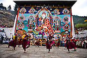 Traditional Bhutanese dancers dance in front of an ancient and giant thanka that is unveiled during a festival in Paro Dzong in Paro, Bhutan. Photo: Sanjit Das/Panos