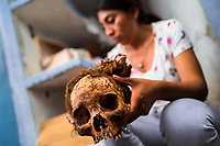 """A young Mayan woman holds a dried-up scull of her deceased grandmother during the bone cleansing ritual at the cemetery in Pomuch, Mexico, 27 October 2019. Every year on the Day of the Dead, people of Pomuch, a small Mayan community in the south of Mexico, visit the cemetery to take part in a pre-Hispanic tradition of cleaning of bones of their departed relatives (""""Limpia de huesos""""). People who die in Pomuch are firstly buried for three years in an above-ground tomb then the dried-up bodies are taken out, bones are separated, wrapped in a decorated cloth, put into a wooden crate, and placed on display among flowers for veneration."""