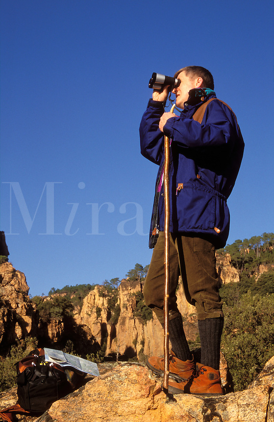 Walker using binoculars at the head of a rocky gorge. Gorges du Blavet, Provence, France.
