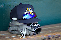 A Charleston RiverDogs cap sits on a glove in the home dugout at Joseph P. Riley, Jr. Park prior to the game against the Greenville Drive on May 26, 2014 in Charleston, South Carolina.  The Drive defeated the RiverDogs 11-3.  (Brian Westerholt/Four Seam Images)