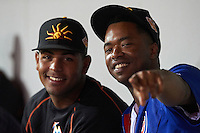 Mesa Solar Sox pitcher Jarlin Garcia (left), of the Miami Marlins organization, and Eloy Jimenez (right), of the Chicago Cubs organization, point to the camera while in the dugout during a game against the Peoria Javelinas on October 15, 2016 at Sloan Park in Mesa, Arizona.  Peoria defeated Mesa 12-2.  (Mike Janes/Four Seam Images)