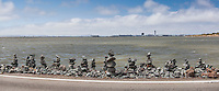 Rock Balancing - an art form or hobby.  Rocky creations rise along the rocky shores of the San Leandro Marina on San Francisco Bay with the Oakland International Airport control tower in the background.