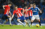 Martyn Waghorn muscles past two defenders and swivels to score his first and Rangers third goal of the match