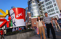 Shopppers in the Tien He district of Guangzhou, China in front the newly opened shopping mall Grandview Plaza pass a large KFC advertisment.  There has been a consuming boom in China that is helping to fuel world economies..07 May 2005