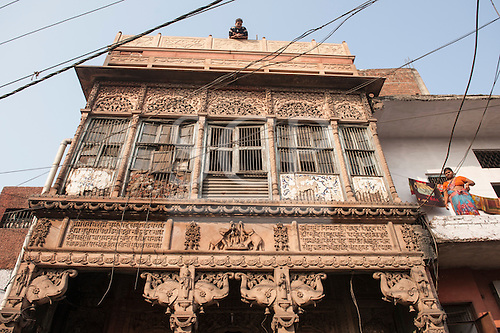 Agra, Uttar Pradesh, India. Richly carved but dilapidated temple to Lakshmi, the goddess of wealth. Elephant carvings and woman on house next door, man on roof.