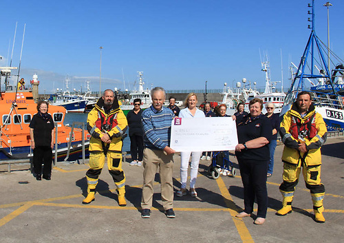 Dunmore East RNLI volunteers receive the check for more than €31,000 from author David Carroll