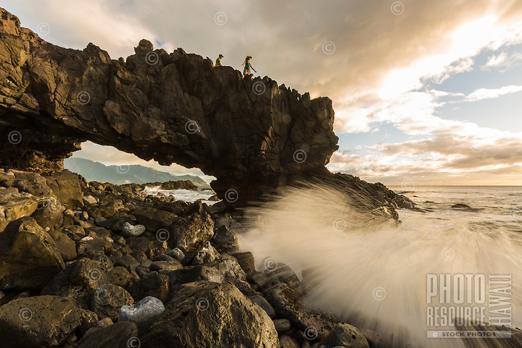 A man and woman hiking the Ka'ena Point trail pauses to take in the view as the sun sets, O'ahu.
