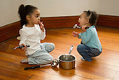 MR / Schenectady, NY. Young children (sisters; aged 1 and 3; African-American and Caucasian) use a pot and spoons as toys to play with, pretending they are making food. Toddler pretends to be eating off of the spoon. MR: Dal4, Dal5. ID: AM-HD. © Ellen B. Senisi
