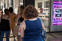 Milan, Italy , july 3 2021 - first day of summer sales woman waiting outside a shop corso vittorio emanuele
